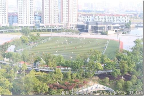從瑞士酒店的高處往下望,可以看到運動場上有很多的民眾在場上踢足球。