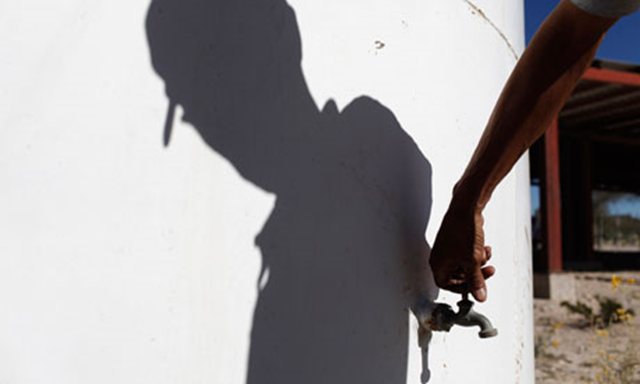 A man turns on the tap of an empty water tank in the Mexican state of Nuevo Leon. Tomas Bravo / Reuters