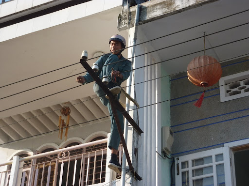 A local workman carefully rewiring the entire district in a single afternoon.