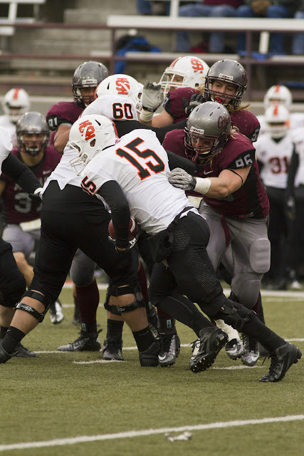 Idaho State quarterback Kevin Yost is chased by Grizzlies Josh Harris (#96) and Zack Wagenmann, while Jordan Tripp watches from afar.  Tripp ultimately made the tackle, a testament of his ability to make plays regardless of field position.  Washington-Grizzly Stadium in Missoula, Mont., October 27th, 2012.