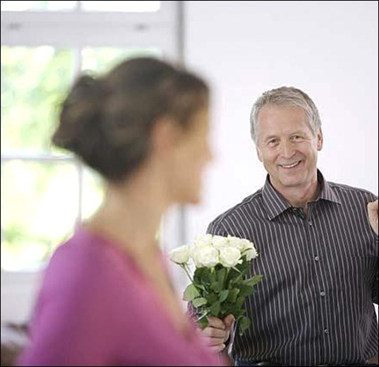 mature_man_holding_white_roses_for_woman_20294