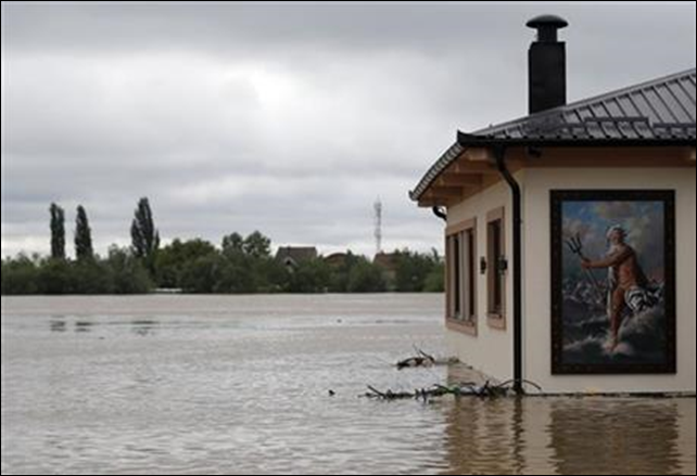 A flooded restaurant with a picture of Poseidon - 'God of the Sea' by the bank of the Sava river in Sremska Mitrovica, 90 kilometers west of Belgrade, Serbia, Saturday, 17 May 2014. Record flooding in the Balkans leaves at least 20 people dead in Serbia and Bosnia and is forcing tens of thousands to flee their homes. Three months' worth of rain has fallen on the region in just three days, and meteorologists say the flooding is the worst since records began 120 years ago. Photo: Darko Vojinovic / AP Photo