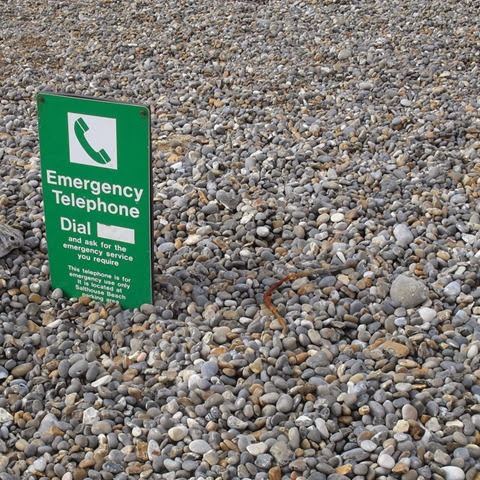 a six foot high sign buried by pebbles after the great storm