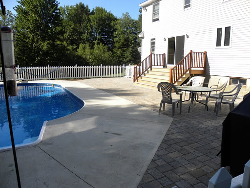 Patio of pavers wraps entire inground pool area at back of house