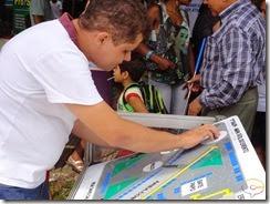 LEGENDA ACESSÍVEL - Imagem mostra Marcos Barbosa do Projeto Um Olhar para a Cidadania lendo um mapa tátil instalado na Praça Pedro II em Teresina durante o Salão do Livro do Piauí - SALIPI 2013
