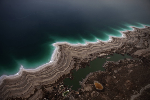 Aerial view of the Dead Sea's receding shoreline. About one-third of the Dead Sea's natural surface area has disappeared and sinkholes are increasingly common as the restorative waters shrink amid drought, diversion of water for agriculture, largely from the Jordan River, and industry pumping. Menahem Kahana / AFP / Getty Images