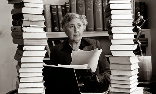 Volume 2, Page 114, Picture, 21. Literature Mystery author and writer, Agatha Christie, pictured at her home, Winter-Brook House, sitting behind her desk with books piled high.