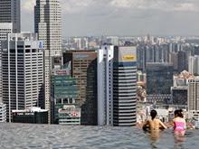 Hóspedes do hotel Marina Bay Sands, em Cingapura, observam a cidade de uma piscina com lateral que termina em queda d'água, no topo do edifício. (Foto: Roslan Rahman/AFP)