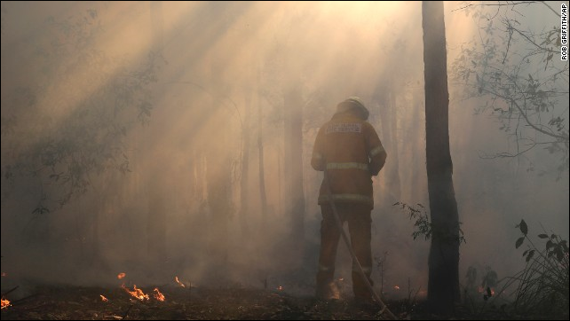 A firefighter mops up on 23 October 2013, after a firestorm swept through Bilpin, Australia. Photo: Rob Griffith / AP