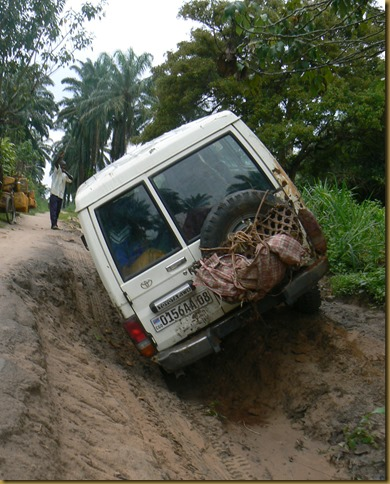 Caught in a hole made by rain in the middle of the road. The basket on the back of the Land Cruiser holds some of Pastor Mboyamba's chickens.