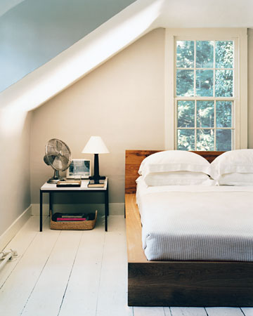 The wide-planked wooden floor's white sheen, along with the light walls and sparse decor, helps offset the dormers in this low-ceilinged guest room.