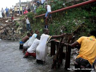 Un groupe des jeunes Kinois tente de récupérer un pont artisanal détruit par la pluie sur la rivière Basoko entre la commune de Bandalungwa et le quartier GB à Gombe, ce 03/04/2011 à Kinshasa. Radio Okapi/Ph. John Bompengo