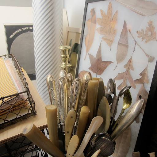A collection of knives with various types of handles and a sampler of leaves can be found in a separate corner of the office.