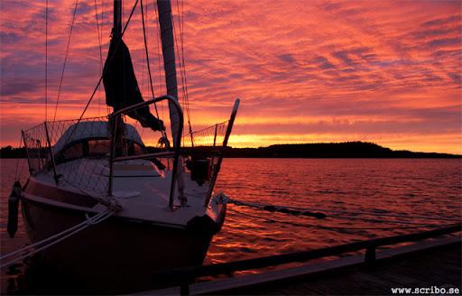 Fantastisk solnedgång vid Bjökö. Segebåt och brygga i förgrunden.