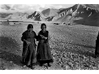 Two cataract patients cross a glacial stream and harsh desert-like landscape to get to the Charang eye camp in outer Mustang, Nepal. <em>© Michael Amendolia</em>