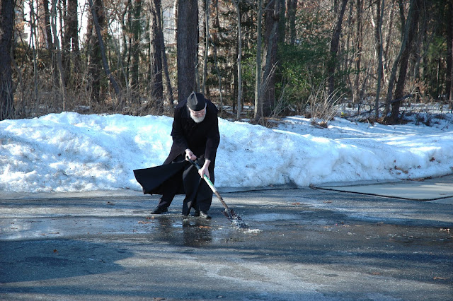 Fr. John breaks up ice on the walkway to the church.