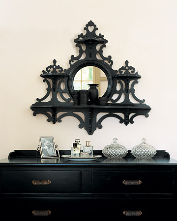 I  love Martha's black bureau. An inexpensive mirror, framed in whimsical fretwork, became a glamorous accent for the bedroom when its old varnish was replaced with a deep, charcoal-gray paint.