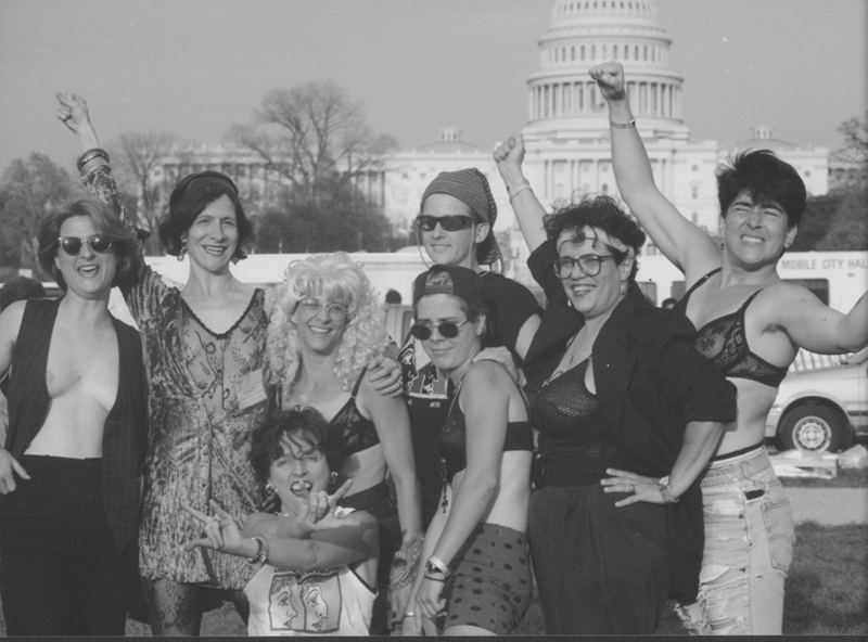 "Lesbian women's band ""Girls in the Nose"" and friends from Austin, Texas, pose with fist-clenched pride at the March on Washington. 1993."