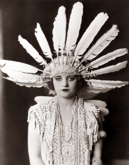circa 1925: Promotional studio portrait of American actor Tallulah Bankhead (1903-1968) wearing a large feather headdress and beaded necklaces, with a dark backdrop.