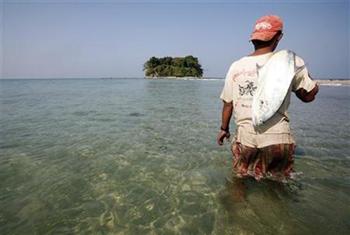 A fisherman carries a fish near Chitthu Island at Ngwesaung Beach, 14 February 2010. Soe Zeya Tun / Reuters