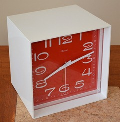 Forestville clock with a white case and red face made in West Germany