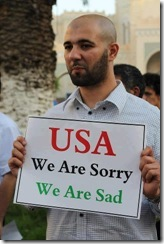 man holding sign that says - USA we are sorry We are sad in response to riots over anti muslim film