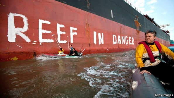 Activists paint 'Reef in danger' on the side of a ship in the port town of Gladstone, Australia. The harbour is undergoing the biggest dredging operation ever approved in Australia. From 2014, huge ships are due to load liquefied natural gas (LNG) from Curtis Island for export, mainly to Asia. Mud crabs, fish and other seafood have erupted in lesions, red spots and other signs of sickness. Getty Images via economist.com