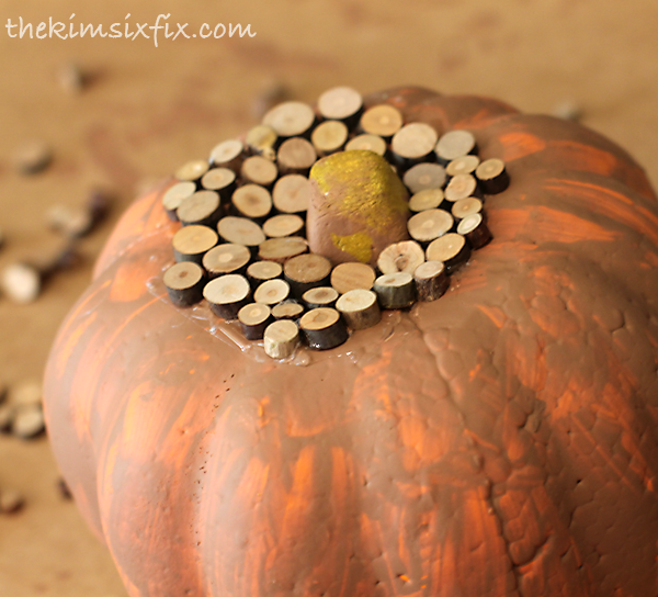 Gluing wood on pumpkin