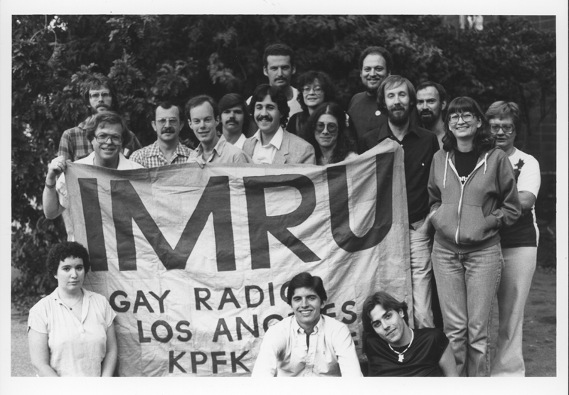 Staff of the IMRU gay radio program on KPFK-FM pose with a banner. IMRU has been broadcasting gay programing in Los Angeles since 1974. Circa 1979.