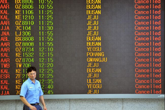 A man walks past an airport board announcing that all flights are cancelled following major typhoon Bolaven at Seoul domestic airport in Seoul on 28 August 2012. The state weather agency issued a typhoon warning on early 28 August 2012 for Seoul, the capital of about 10 million people, as the storm named Bolaven continued moving northwards. JUNG YEON-JE / AFP / Getty Images