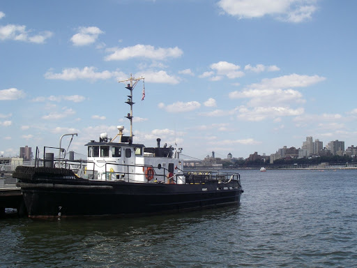 In the foreground, the Swivel, a 40-something tugboat used by GIPEC (the group that runs Governors Island) as a ferry for personnel & the like. Way off in the distance, one of the escort boats sees the Long Island City Boathouse gang safely to the Brooklyn shore. They did a nice job, those escorts.