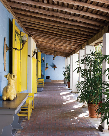 I love that these shutters were painted a canary yellow against the sky blue walls. (Martha Stewart Living)