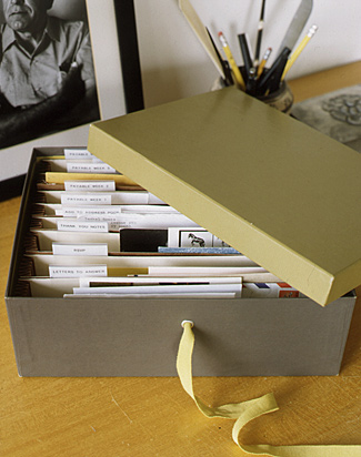 A recycled shoebox can be customized with a grommet and ribbon to hold mail and small papers.