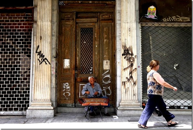 epa02812998 A woman walks past a street musician amidst closed shops in central Athens, Greece, 07 July 2011. Many shops in Athens' main shopping district have gone out of business amidst an economic crisis and recession. EPA/ORESTIS PANAGIOTOU +++(c) dpa - Bildfunk+++
