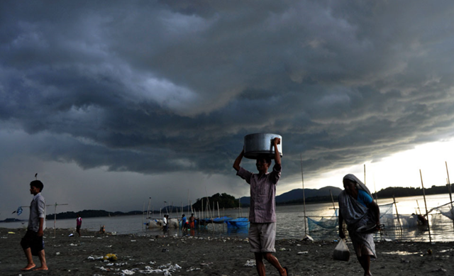 Rain clouds loom over the Brahmaputra river in Guwahati, capital of northeastern Assam state, 28 August 2013. The monsoon season, which runs from June to September, accounts for about 80 percent of India's annual rainfall. However, the flooding also causes hundreds of deaths and damage to infrastructure, homes and farms. Photo: Biju Boro / AFP