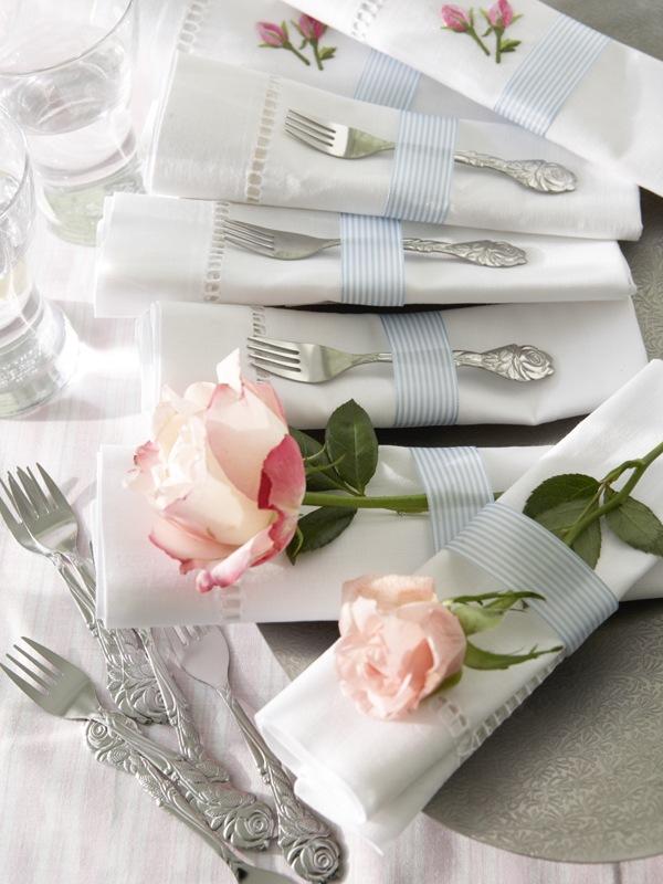 Die mit Rosenknospen bestickten Hohlsaumservietten werden mit Schleifenband umbunden. Wahlweise werden echte Rosen oder Kuchengabeln mit Rosenmotiv hineingesteckt.<br />Feine Gestecke Ohne Rosen oder Rosenstickerei kommen die Hohlsaumservietten nicht auf den Tisch. Ein hellblaues Schleifenband hält alles zusammen ? Kuchengabeln sind auch mit im Bund