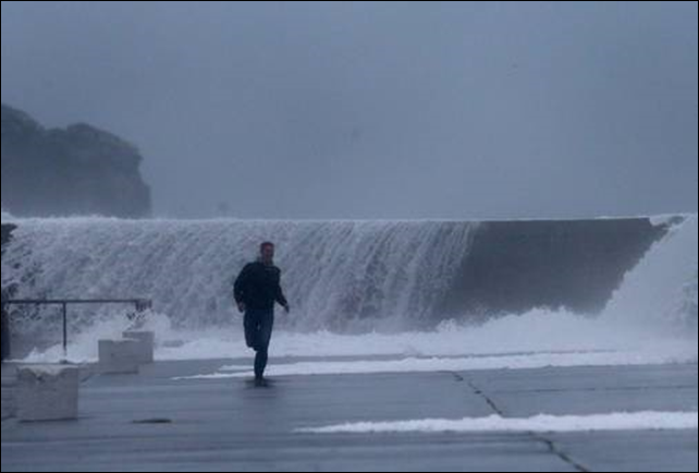A man runs from waves crashing onto the East pier in Howth, Dublin, 4 January 2014. Photo: Irish Independent