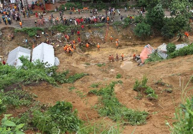 Rescuers search for bodies under a landslide Chittagong, Bangladesh, on Wednesday, 25 June 2012. AFP / Getty Images
