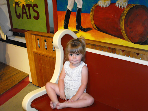 Little Miss Alli is sitting on one of the carosel benches