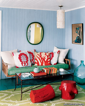The play between rug, cushion, floor vase, painting, and the wall color is brilliantly arranged. The warmer colors add sensation. (www.marthastewart.com)