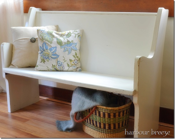 Painted Old church Pew (in an off white color) with 2 pillows sitting on it with a basket of blankets underneath