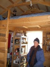 Stillwood stands inside the cabin she built by hand, without using any power tools. The bedroom loft is above her. (Photo credit: Jennifer Moore)
