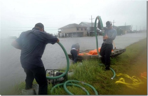 Plaquemines Parish emergency workers rush to lay out tubes to be filled with water to heighten a levee following heavy rains from Tropical Storm Lee that hit the area September 3, 2011 in Myrtle Grove, Louisiana. The U.S. National Hurricane Center (NHC) warned of heavy rain across southeastern and south-central Louisiana and forcasted that the storm would continue its slow, potentially erratic motion toward the north or northwest over the next day.