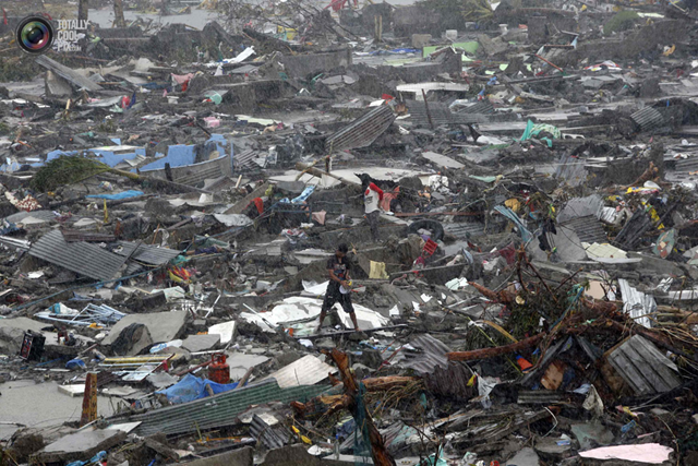 A man stands atop debris as residents salvage belongings from the ruins of their houses after Typhoon Haiyan battered Tacloban city in central Philippines. Photo: ERIK DE CASTRO / REUTERS