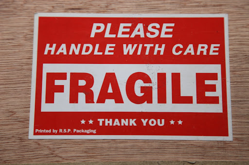 The sign says 'FRAGILE' so we better be careful.