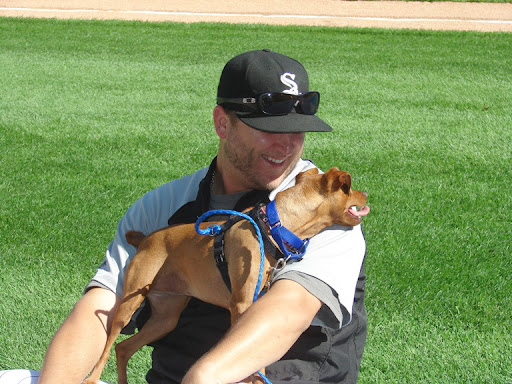 A lucky adoptable pooch cuddles with Mark on the field before a game.