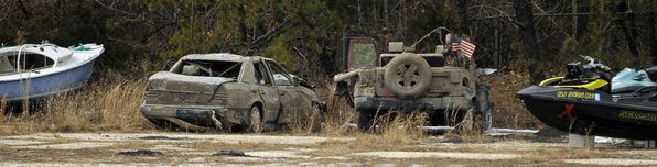 At a fenced compound in Brick, New Jersey, hulks of ruined vehicles removed from Barnegat Bay await their next stop while in storage. The cleanup cost from Hurricane Sandy will depend on how much debris is collected, officials said, but it will likely be in the tens of millions. Photo: Philadelphia Inquirer