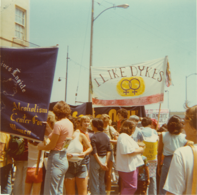 "Alcoholism Center for Women group preparing to march in the Los Angeles Christopher Street West pride parade. Album caption reads: ""We ended up one of the largest contingent, and everyone wanted to march next to us. We got to go 2nd, after Parents & Firends of Gays. Stonewall followed after us."" 1977"