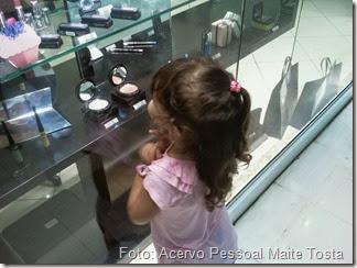 Esther olhando vitrine de maquiagem