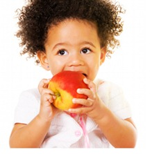 Pretty little girl biting an apple